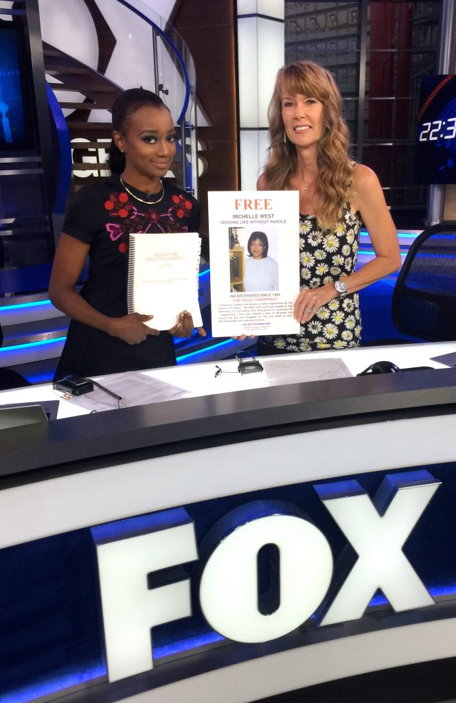 Miquelle and Amy hold up Michelle's clemency petition and CAN-DO poster